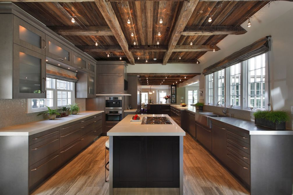 This kitchen mixes a modern look with a rustic ceiling and exposed electrical conduits.